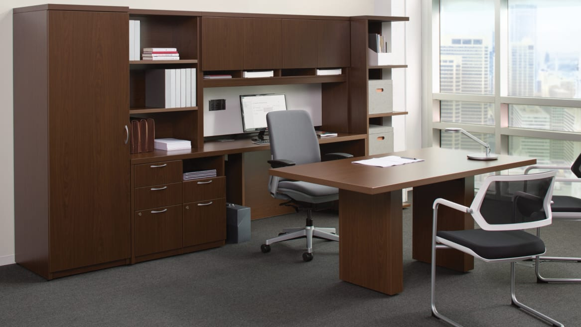 Payback table in front of large Payback desk with storage and shelving