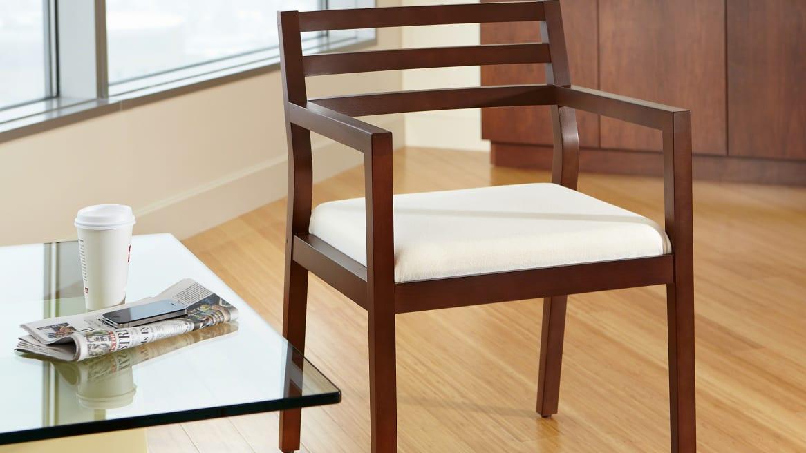 Medium Walnut Sawyer Guest Chair next to a glass coffee table