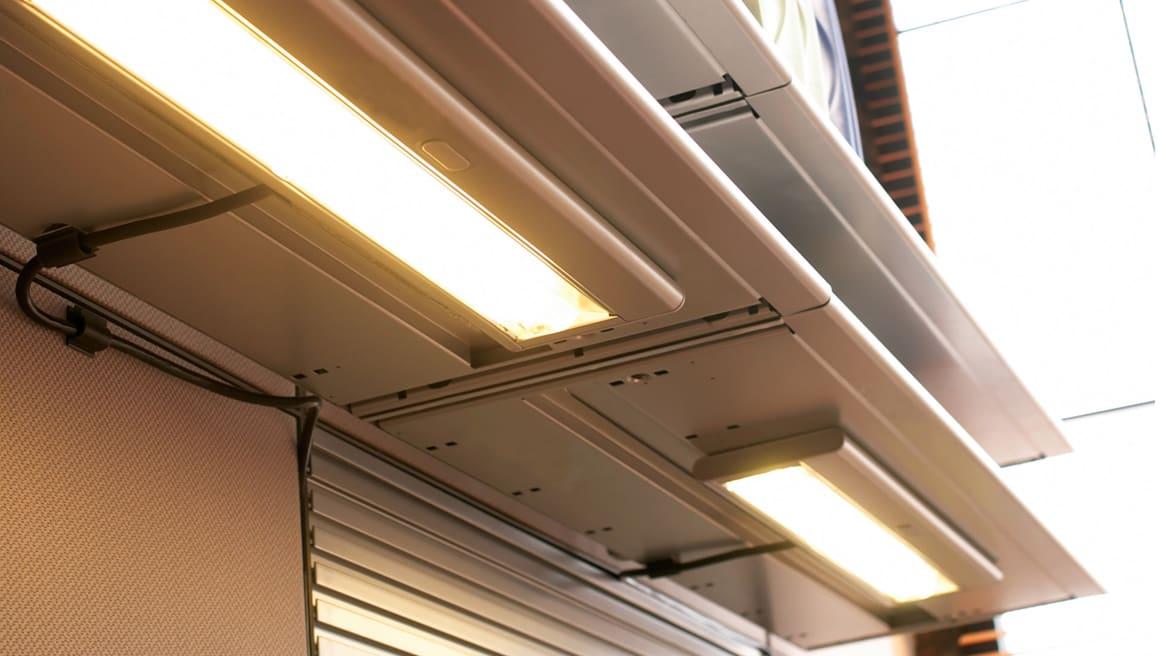 2 Shelf Lights mounted under shelves of workstations