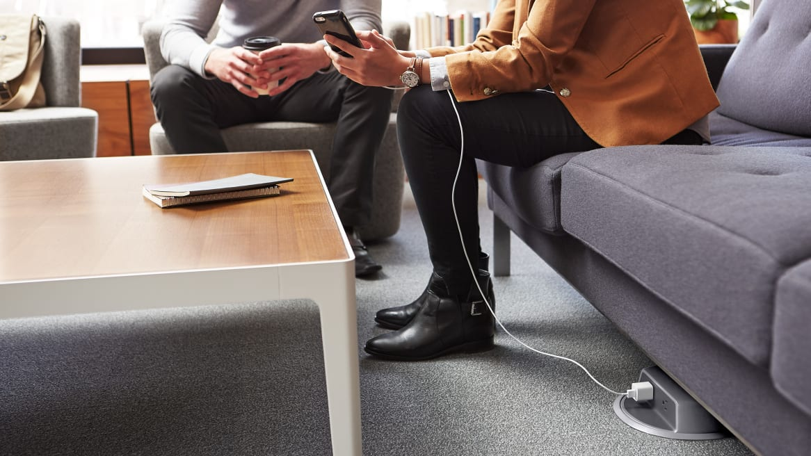 Two people from waist down sitting on a couch with a Nema Monument Connector Cover Thread Power Distribution under the couch charging a phone in a on of the people's hand