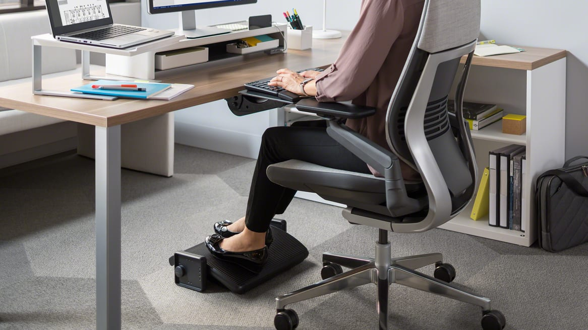A woman sitting at a workspace with her feet on black Footrest under her desk