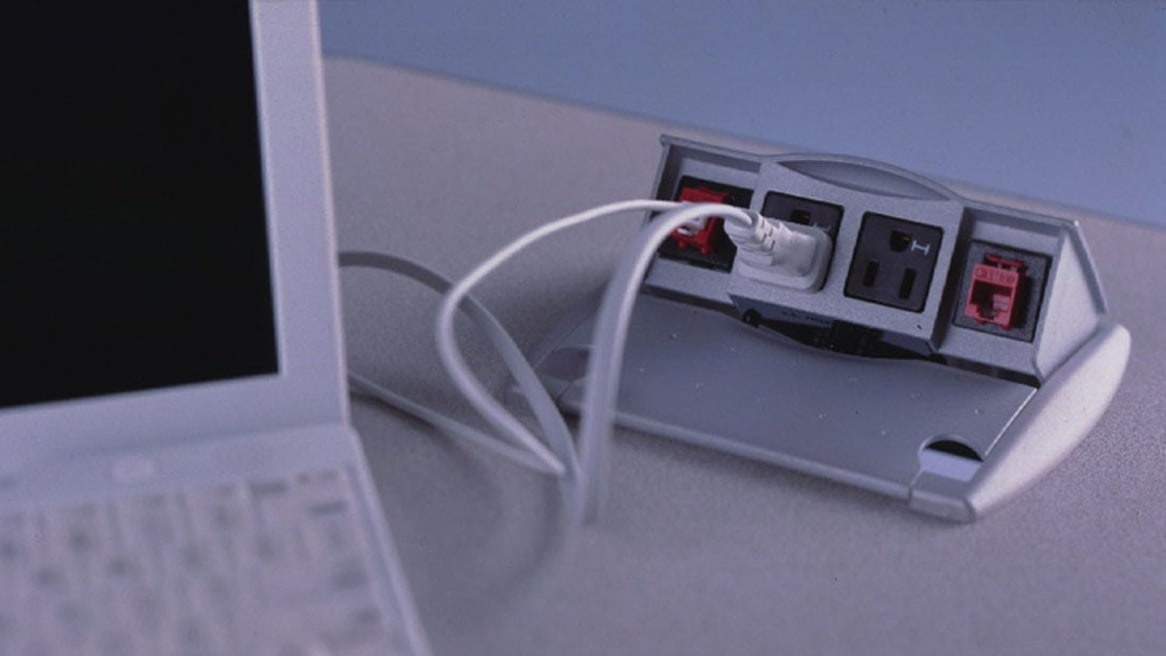 A laptop computer is plugged into an outlet built into the top of a table