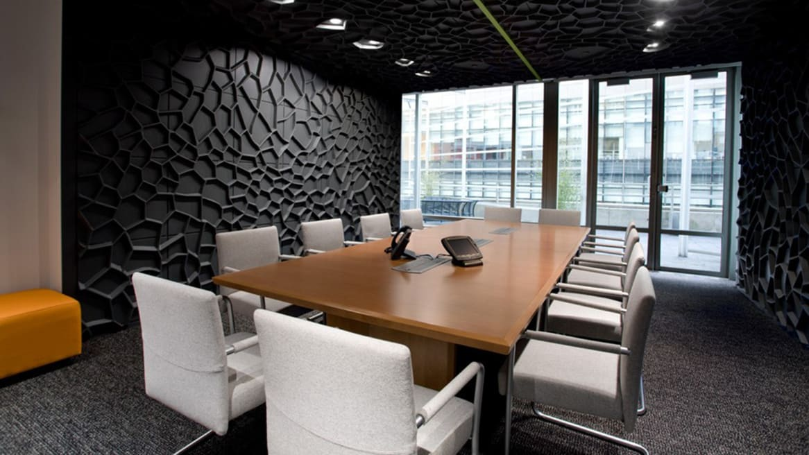 In a conference room with black textured accent walls, several chairs with white upholstery are arranged around a Coalesse E-Table 2