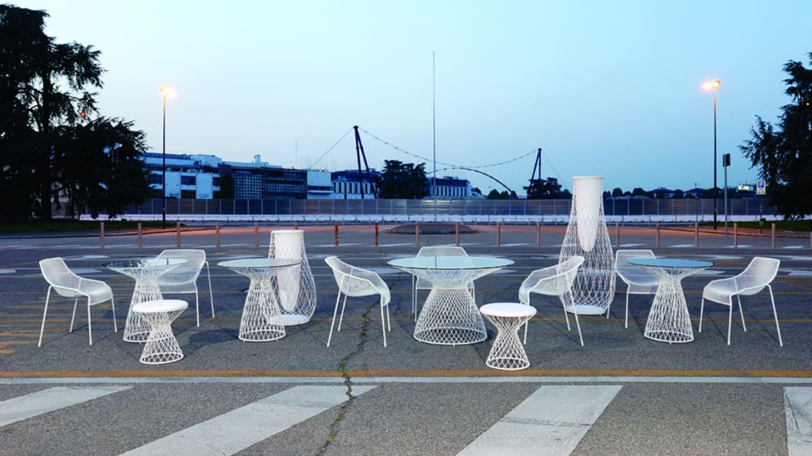 Collection of Emu furniture, including chairs, tables, and vases, outside in a parking lot