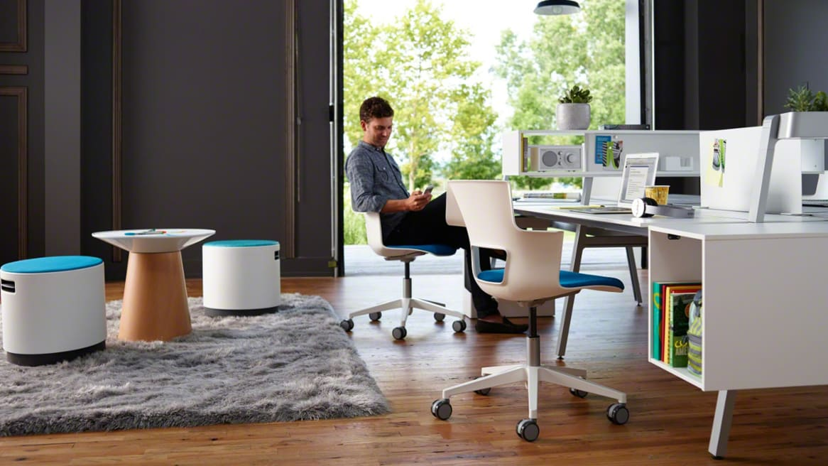 A man looking at his phone while sitting at a Bivi desk on a Shortcut task chair next to a rug with Campfire Paper Tables