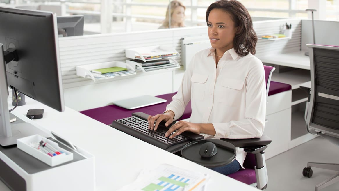 A woman typing with a Keyboard Platforms + Mechanisms at a desk