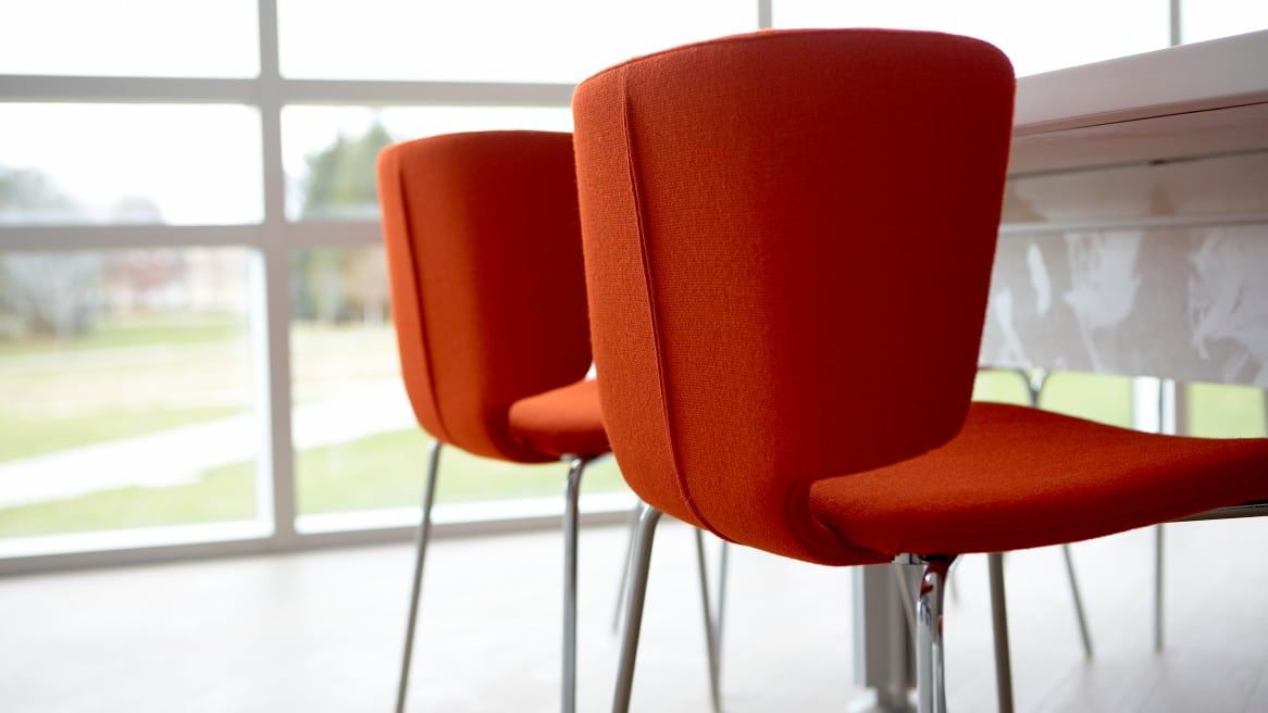 2 red Wrapp Chairs next to a white table