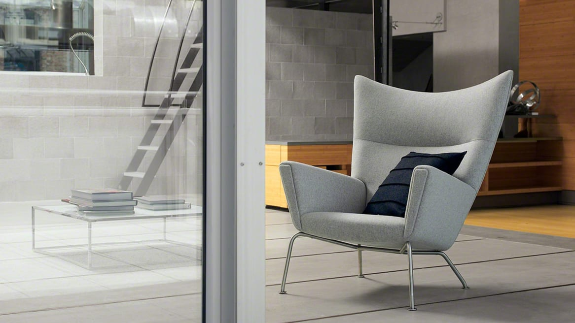 Grey Wing Chair CH445 with a black throw pillow on it in a lounge area