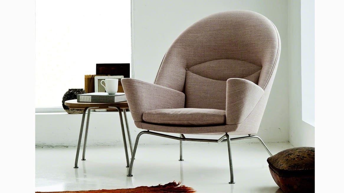 Grey Oculus Chair CH468 next to an end table in a corner of a white room