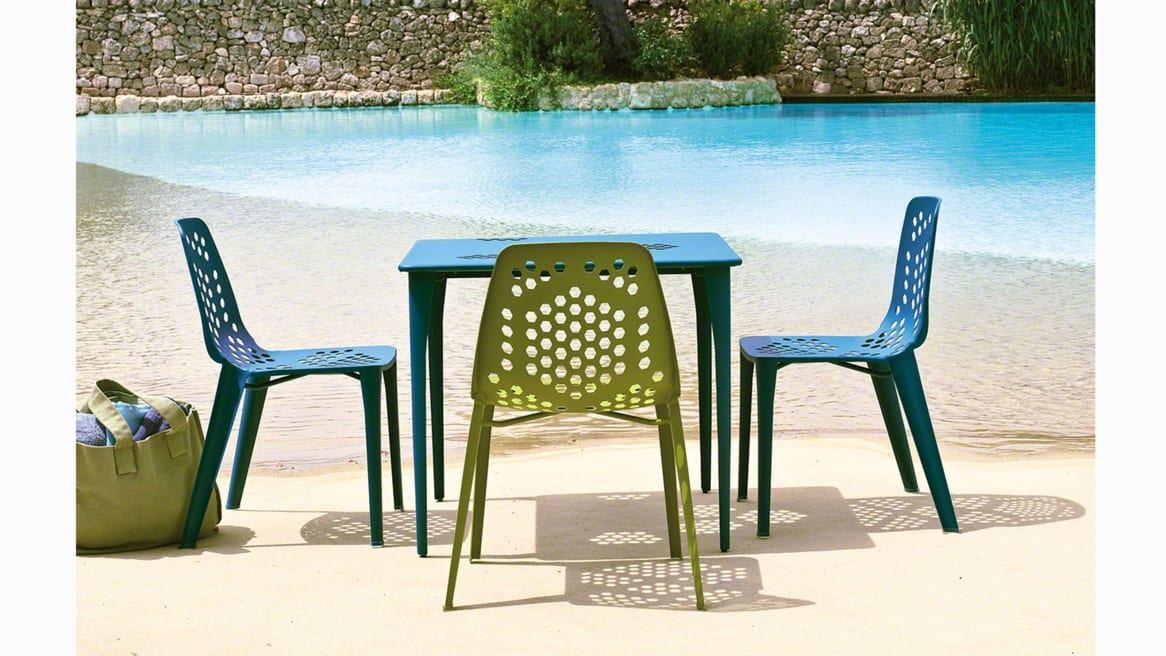 Blue and Green Emu Pattern Seating around a table in an outdoor area next to a pool