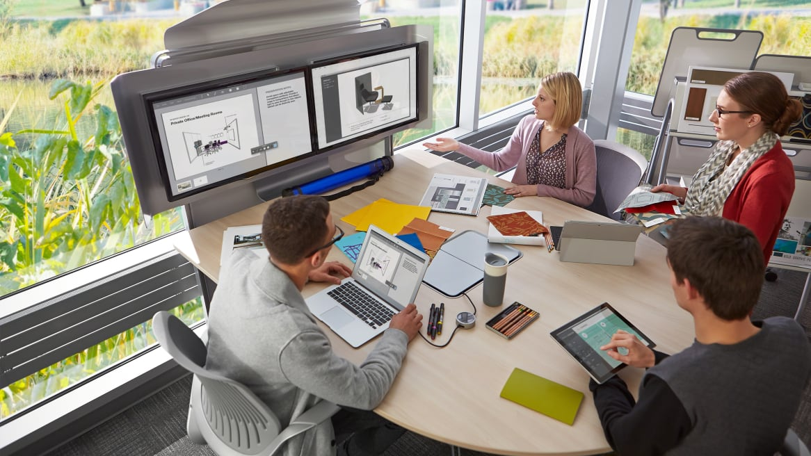 Four co-workers sitting around a Bivi Half Round Table looking at a media:scape