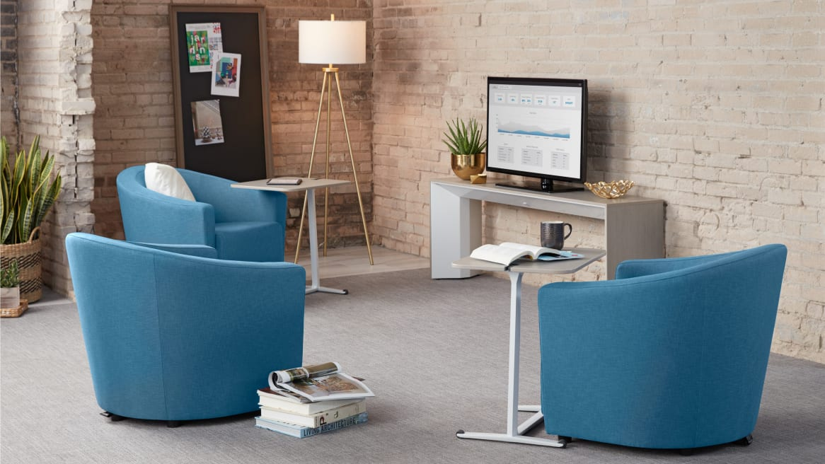 Three blue Jenny Round Low Lounge Chairs in a lounge area in front of a TV