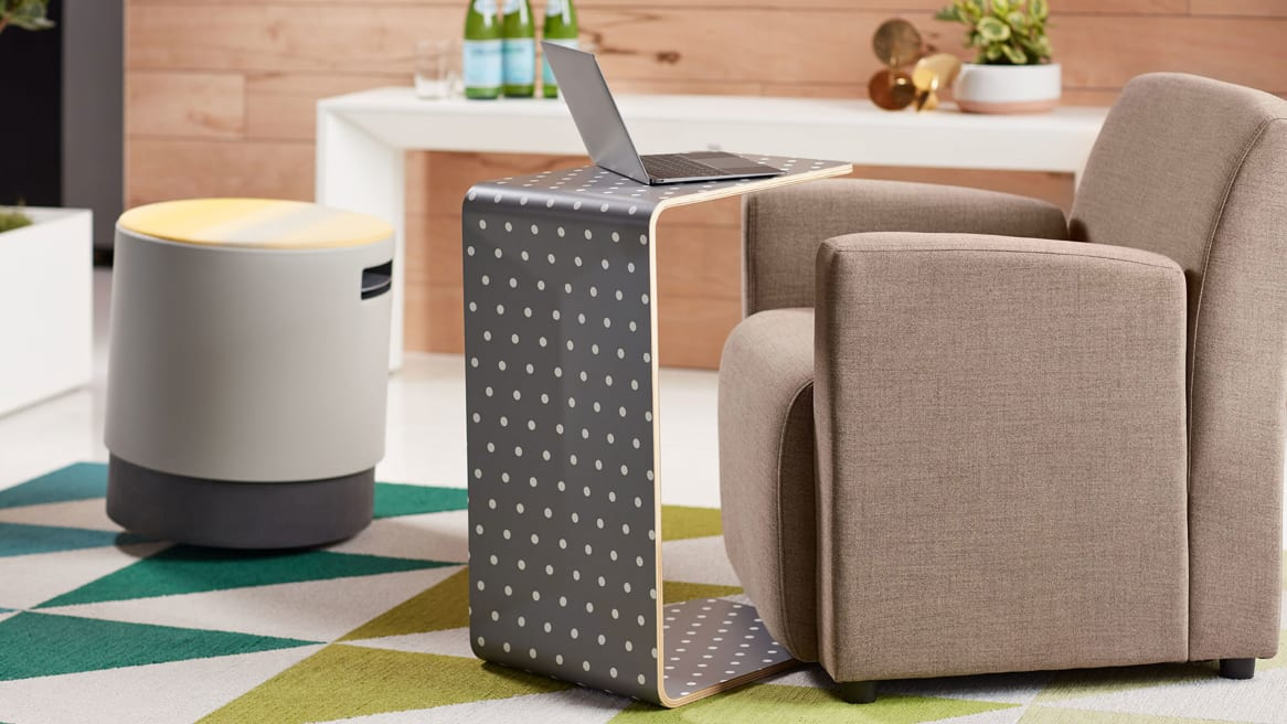 A polka dot Campfire Personal Table with a laptop in front of a Jenny Low tan armchair