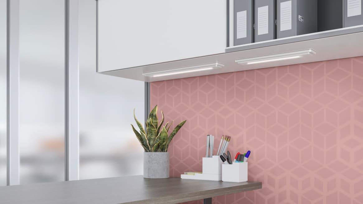 LED Shelf Light under overhead storage, pink wall.