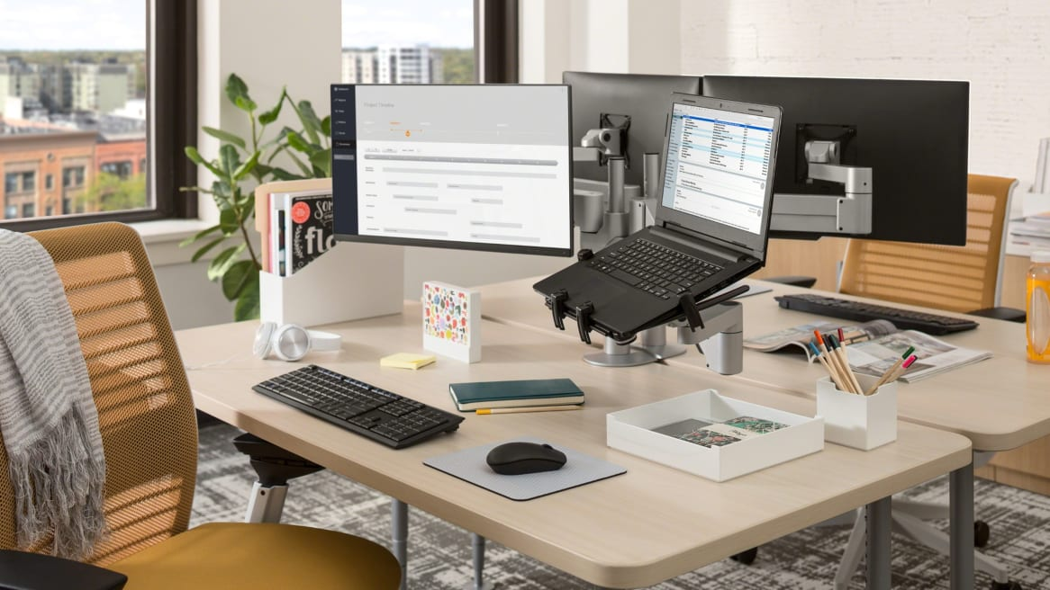 Two desks with CF Series Monitor arms and a Universal Laptop/Tablet Holder holding a laptop