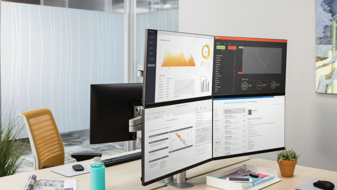 Four computer monitors being supported with Steelcase CF Series monitor arms in two-over-two configuration