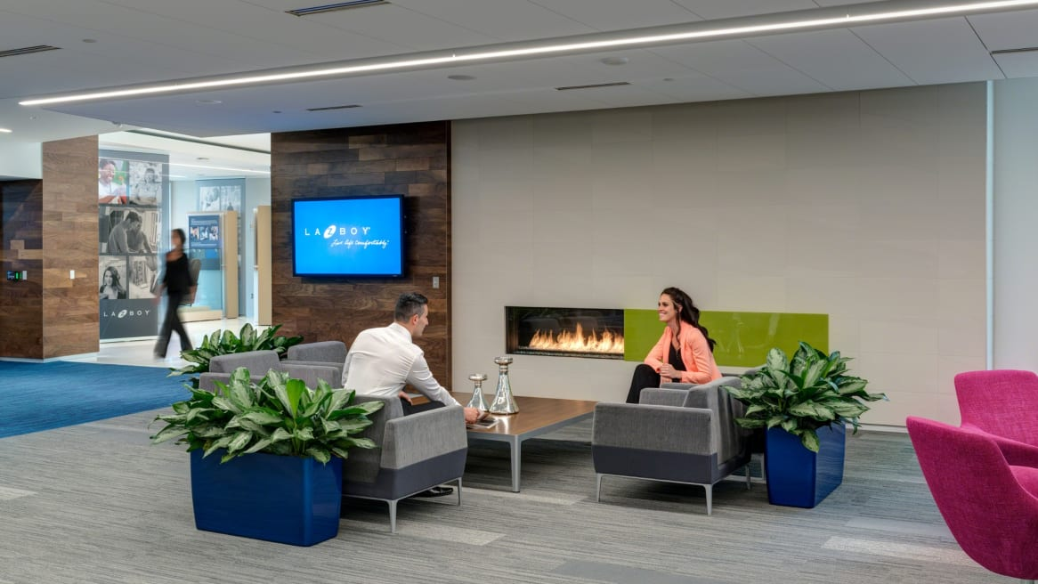 Man and woman chatting while seated on gray sofas with a fireplace in the back in an open area. A woman walking by the place.