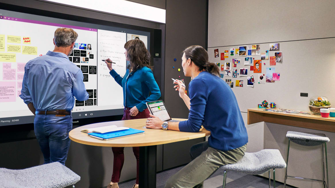 Three persons collaborating while drawing on interactive ideation hub surface