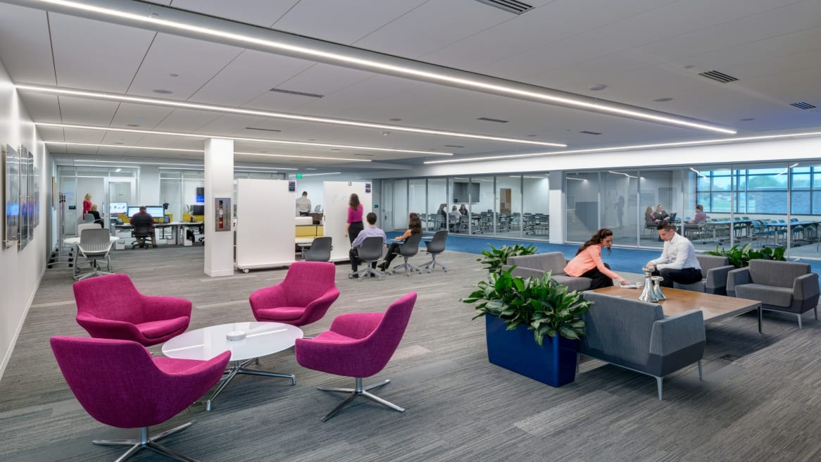People collaborating on a open area with different products such as whiteboards, grey lounges, Node chairs.