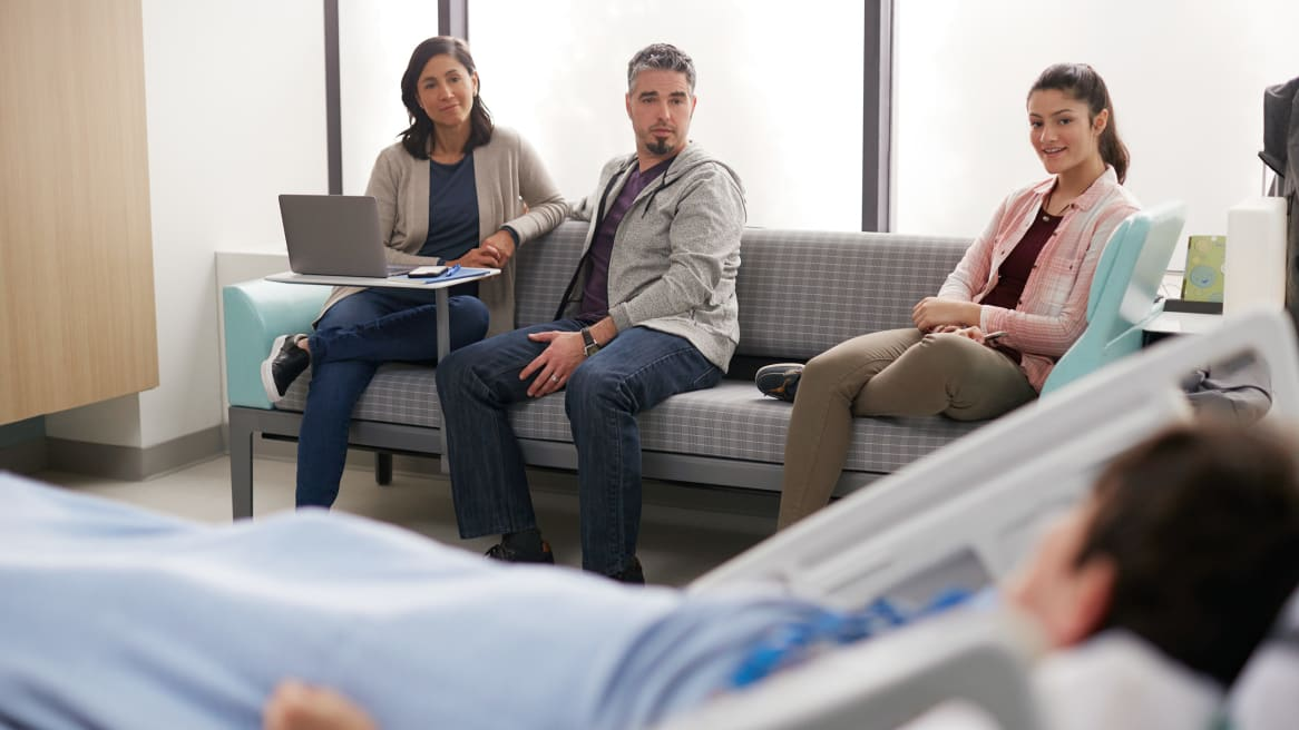Family sitting on a Surround sleeper sofa observing a sick family member