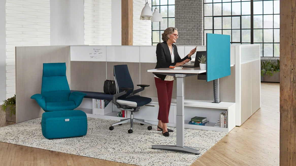 Woman working on a Ology height-adjustable desk with blue Universal Modesty Screen