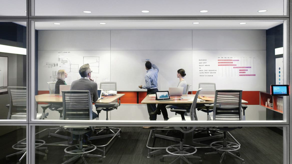 people working and collaborating while a man is writing on a whiteboard inside a meeting room