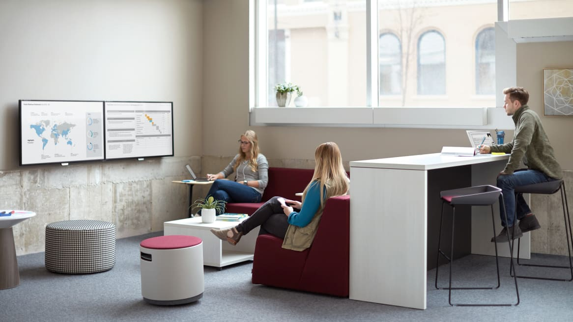 Three people work together in an office collaborative space. Two women sit on Campfire lounge sofas with a Turnstone Buoy and a Campfire Ottoman also featured. A man sits nearby on a Scoop stool while working at a Campfire table.