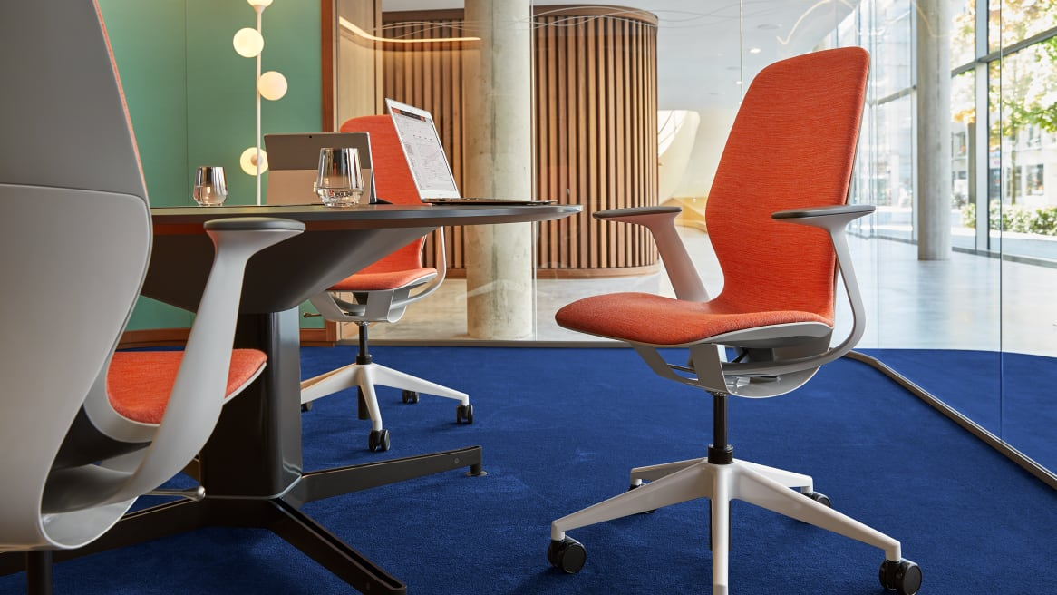 Three SILQ chairs with orange upholstery are shown in a conference room with glass walls and a deep blue rug on the floor