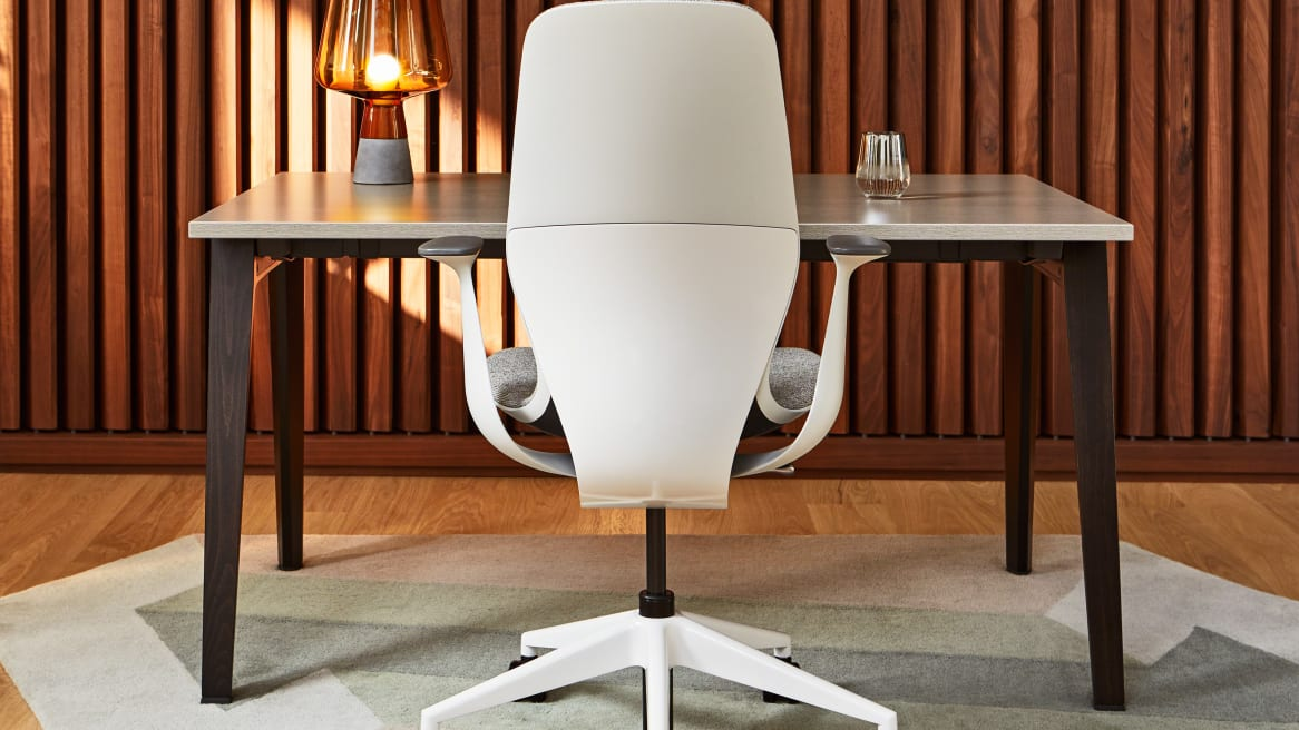 A SILQ office chair with gray upholstery is shown at a wood table with the back of the chair facing the viewer