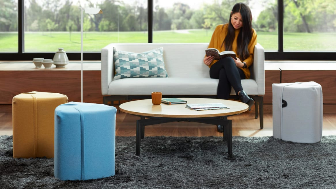 A woman sits on a Bivi Rumble Seat in a lounge that also features Campfire Pouf seating and a round Bassline occasional table