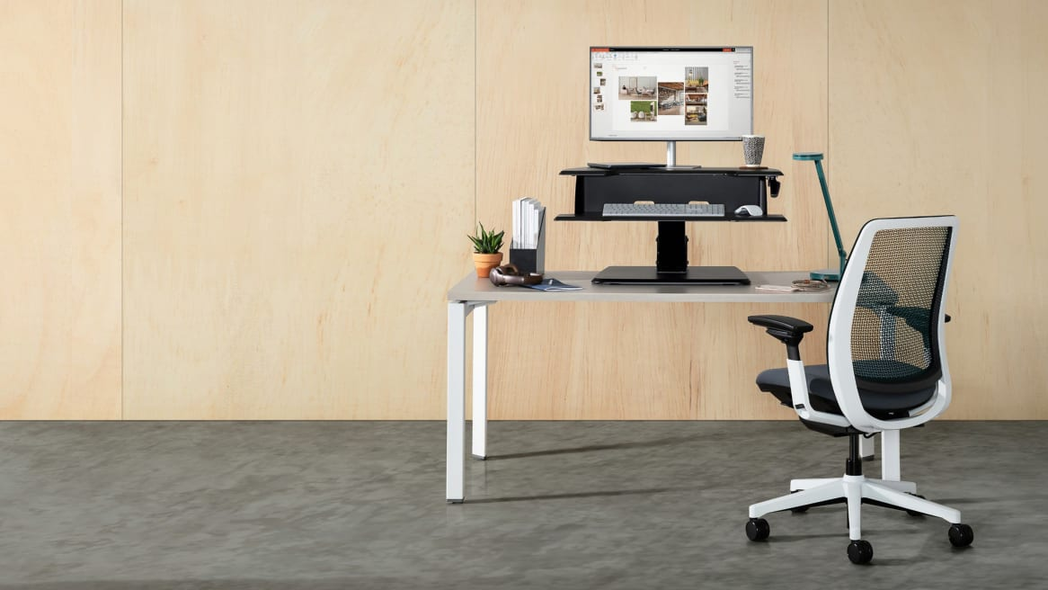 An Active Lift Riser from Steelcase is used on top of a Currency Martin desk with an Amia chair next to it