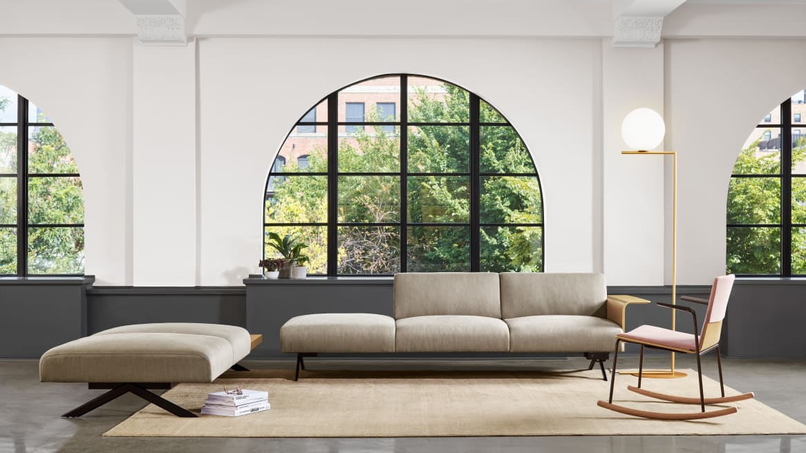 An office lounge area with windows features a Sistema lounge system and Montara650 rocker chair