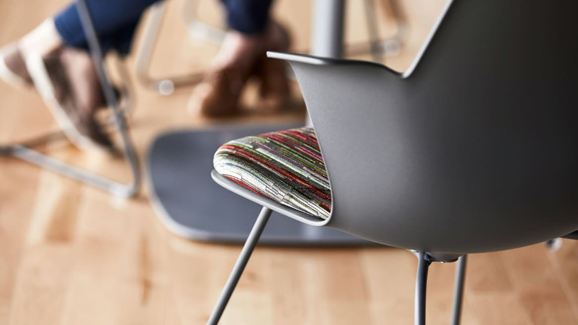 A close-up photo of the back of a gray Node X base chair with multi-colored seat upholstery