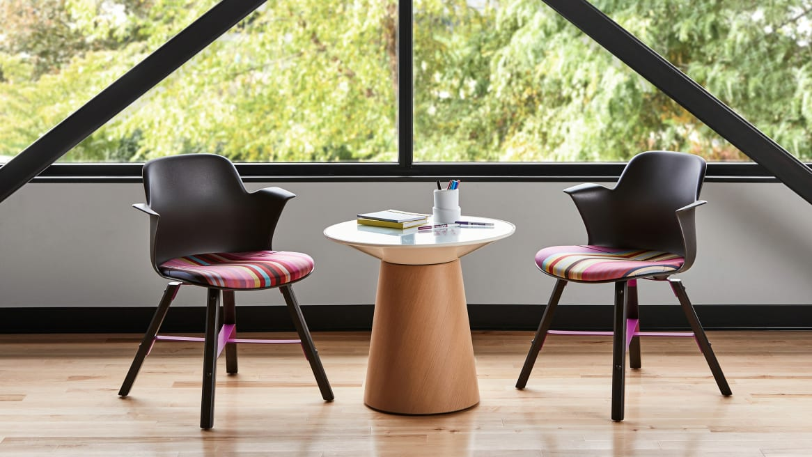 Two Node chairs with wood legs and striped, multi-colored seat upholstery are shown next to a Campfire Paper Table