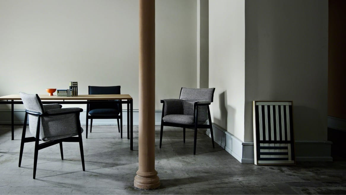 Three Embrace chairs CHE005 by Carl Hansen & Son placed near a table with a column in the foreground