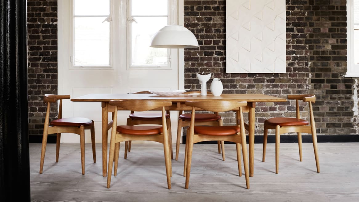 Elbow chairs around a CH327 dining table by Carl Hansen & Son