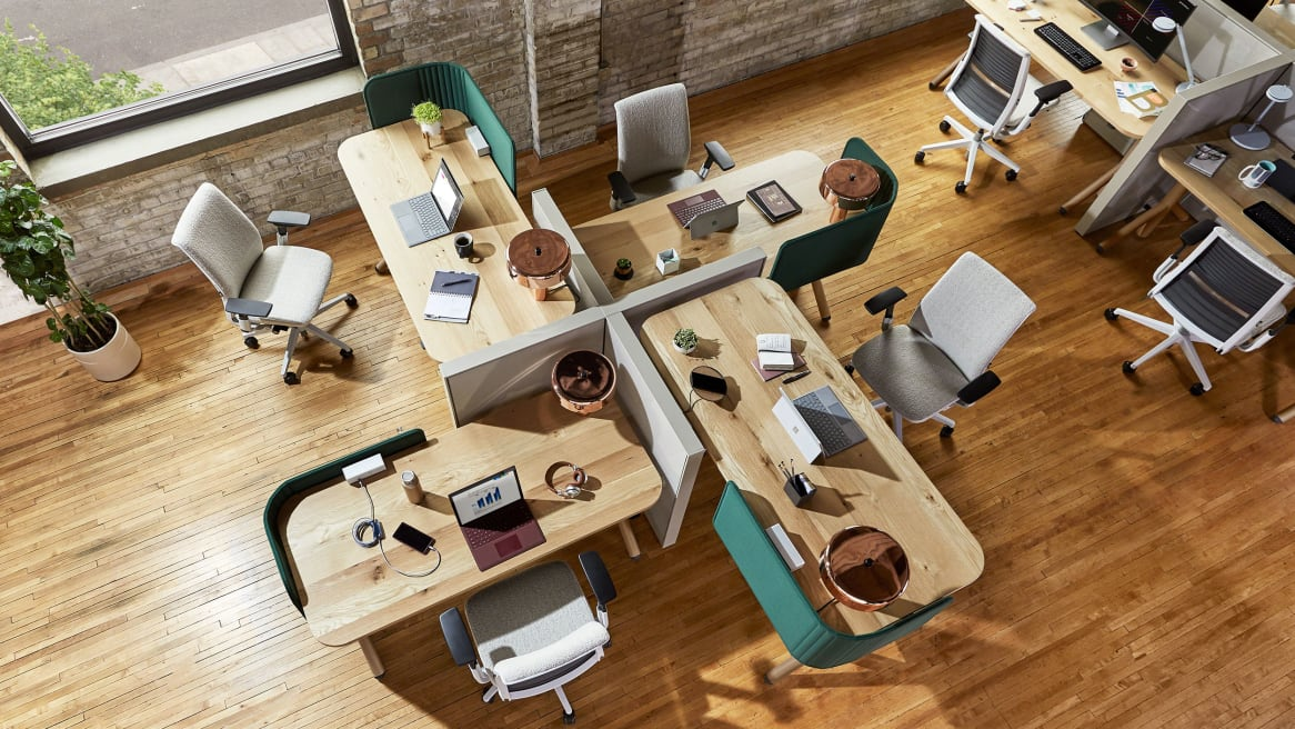 An overhead view shows a workstation created using Steelcase Flex height-adjustable desks, screens, and Think chairs