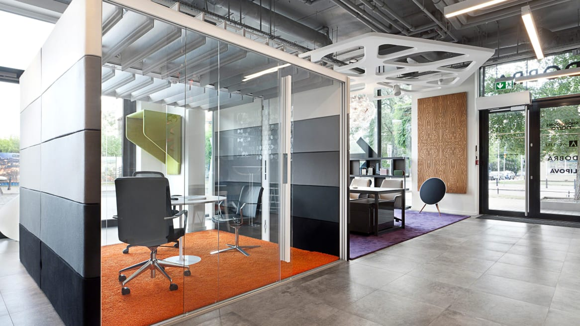 An Orangebox Air pod is seen in an office setting next to a lounge with three desk chairs arranged around a table