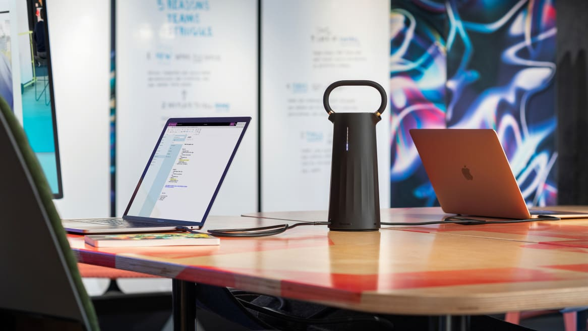 Steelcase Flex Mobile Power is shown sitting on a table between two laptops