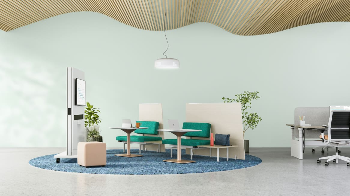 Lounge setting with Sylvi Lounge System, Back Panels, and Ganging Tables. A Think desk chair is seen at a nearby workstation.