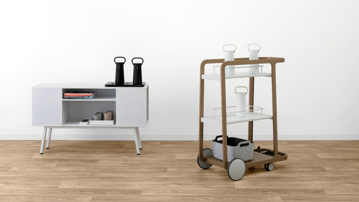 Many black and white Flex Mobile Powers on top of a white credenza and a Steelcase Flex Cart.