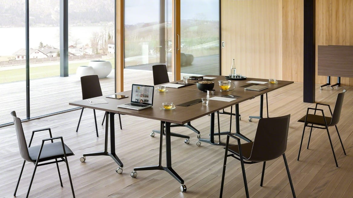 Large brown table with a laptop, glasses and papers on it, there is also 5 arm chairs