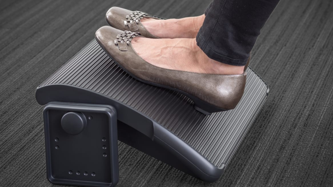 Woman's feet with shoes on top of a black Steelcase Footrest