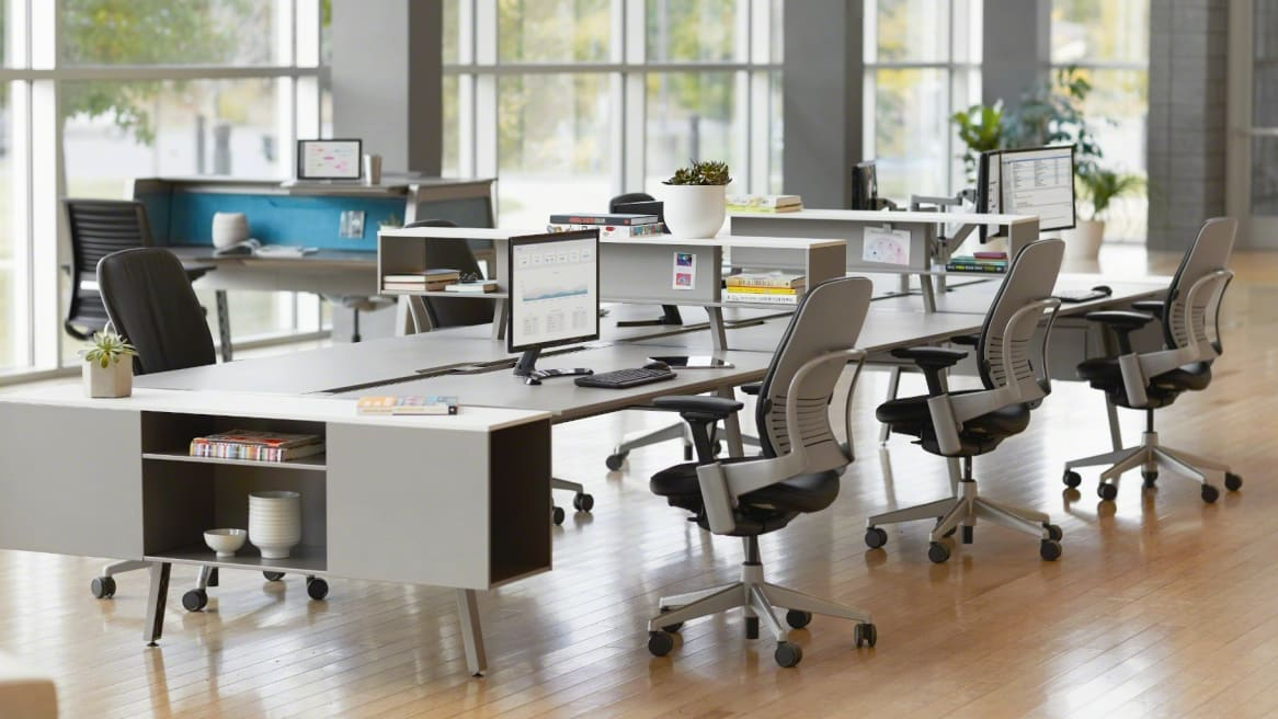 Work area with white collaborative desks and blue Leap chairs