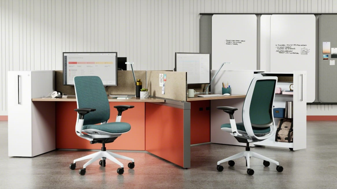 Work area with two height adjustable desks divided with a screen and two blue Series 2 chairs