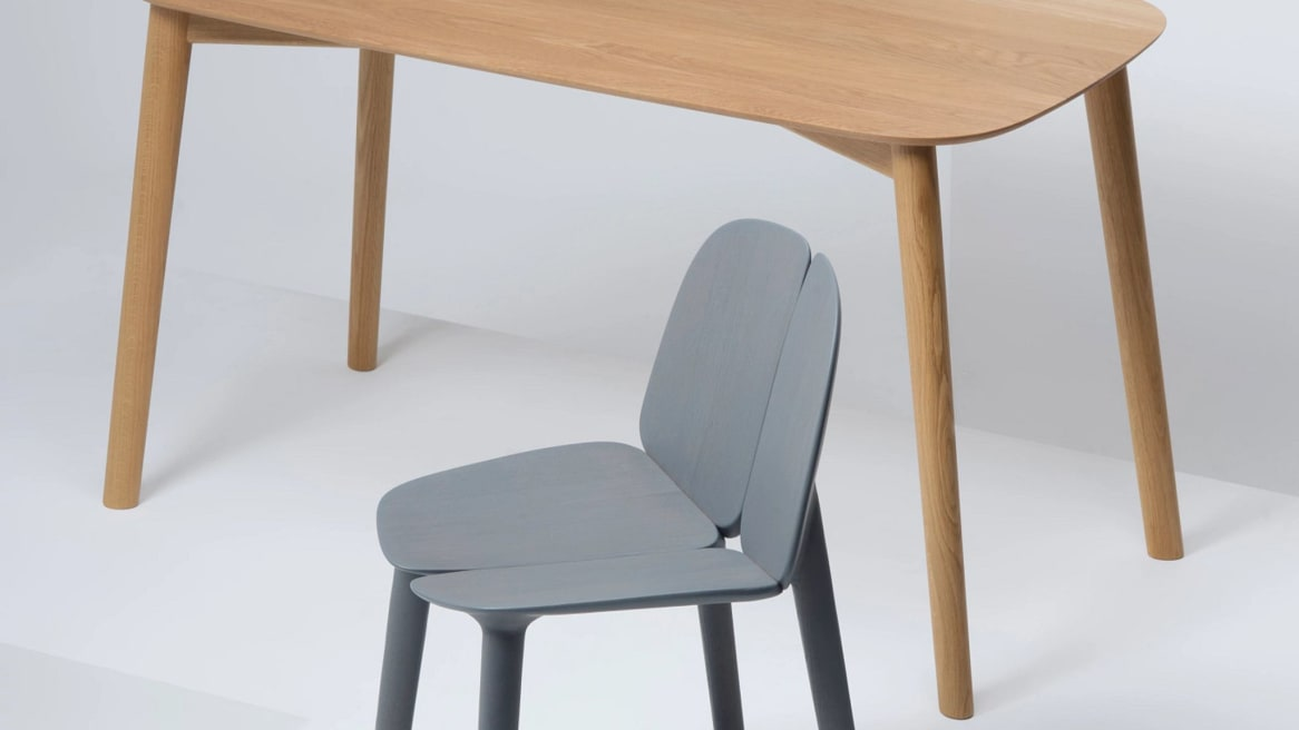 A gray Mattiazzi Osso Chair in front of a natural oak Osso Table