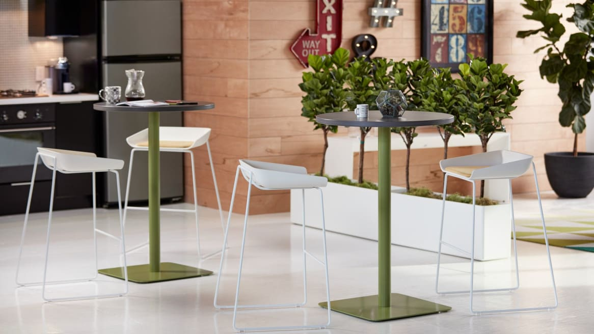 round simple tables with green legs in a cafeteria