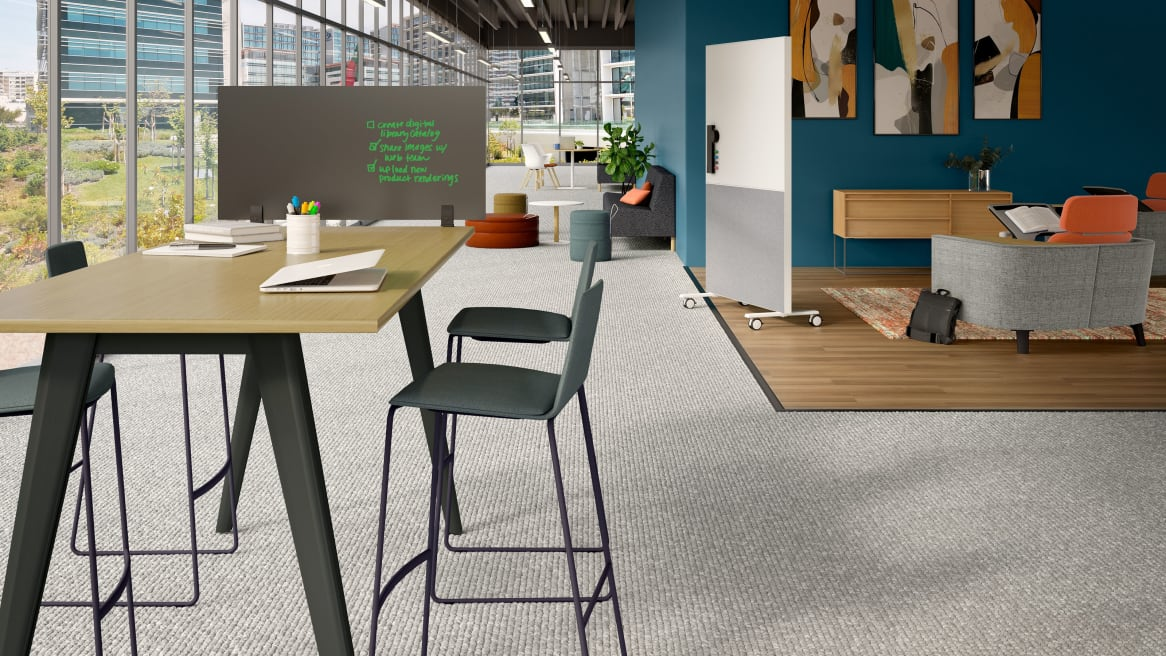 Office space equipped with PolyVision Boundri™ screen dividers, a high table and gray stools.