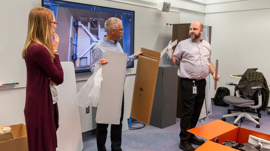 two men and a woman holding and unboxing new products such as screens
