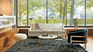 An Avery chair and Cara sofa by Mitchell Gold + Bob Williams in a lounge setting with a Bassline table nearby